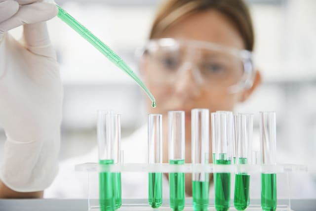 Lab Technician Using Pipette --- Image by © moodboard/Corbis
